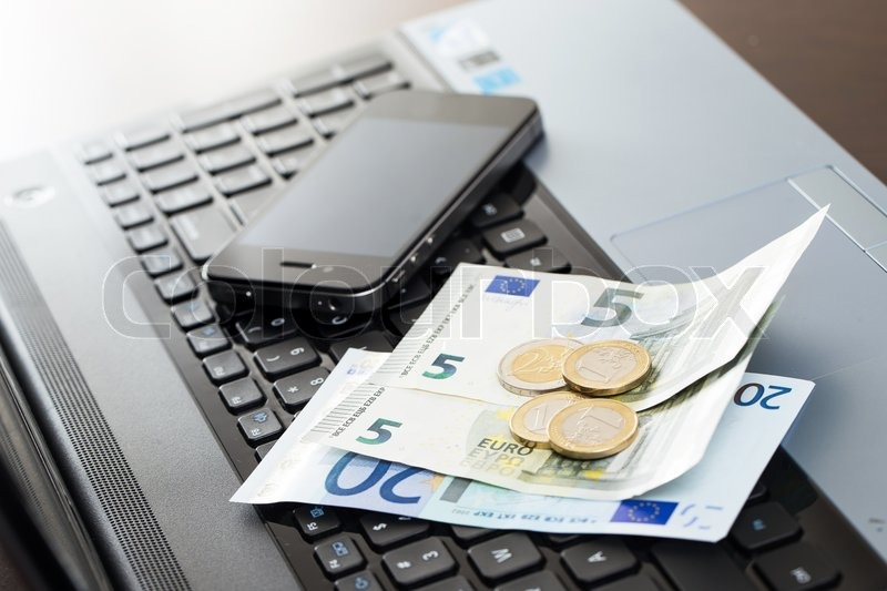 Stock image of 'Laptop, mobile and cash on the table'