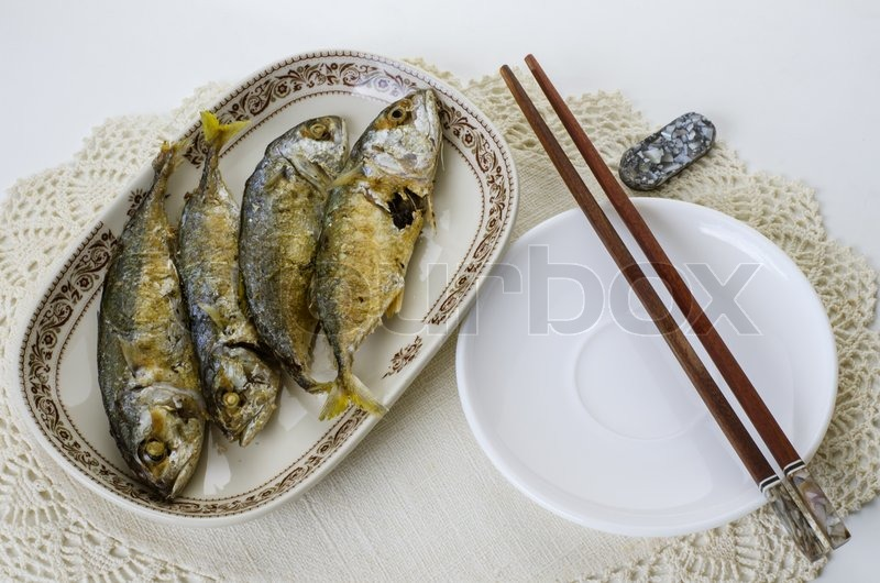 Stock image of 'Fried indian mackerel in ceramic dish with chopstick'