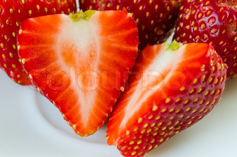 Stock image of 'Fresh red sliced strawberries in white dish'
