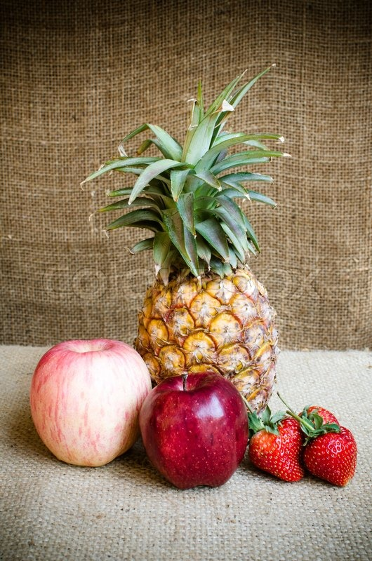 Stock image of 'Fresh red and light red apple and pine apple behind'