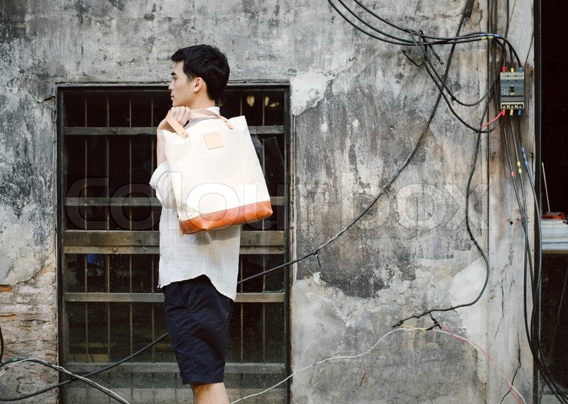 Stock image of 'Attractive man with canvas bag on grunge concrete background, fashion concept'