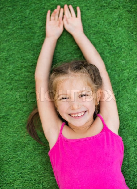 Stock image of 'Little cute girl lying on green grass'