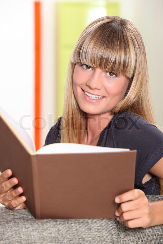 Stock image of 'Young woman with blunt fringe reading a book'