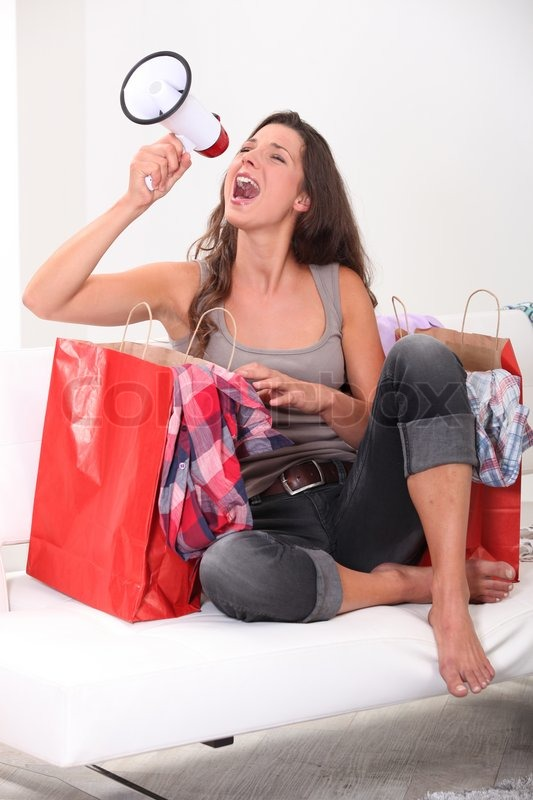 Stock image of 'Studio shot of a woman with shopping bags and a loudspeaker'