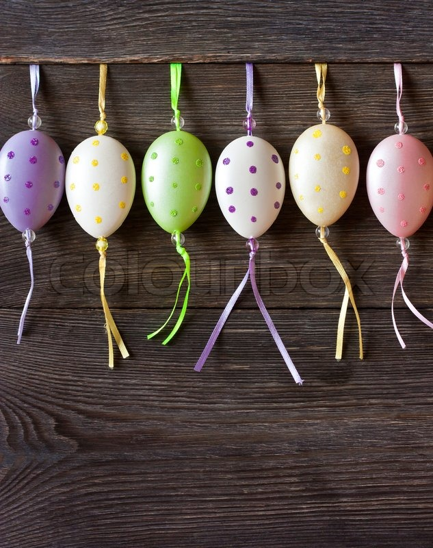 Stock image of 'Colorful Easter eggs hanging on wooden background with copy space for text.'