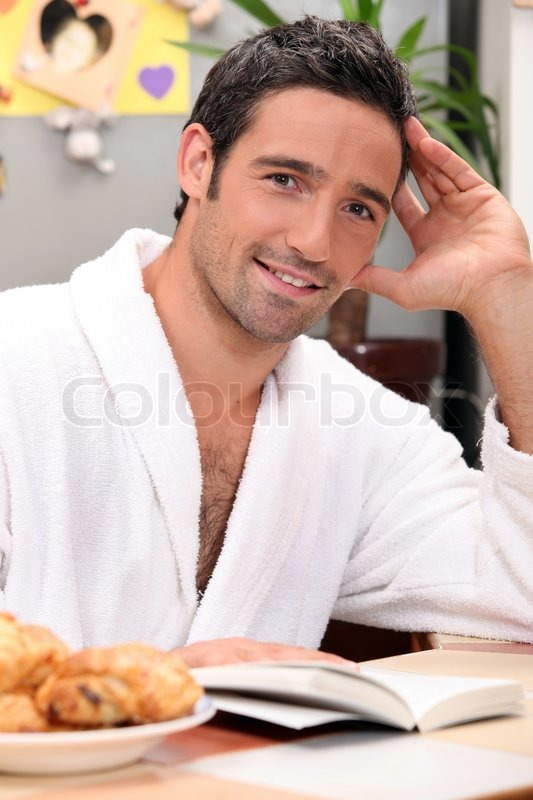 Stock image of 'Man reading a book at breakfast'