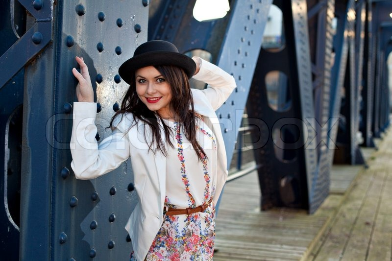 Stock image of 'Young pretty girl elegantly dressed posing on old iron bridge. Cute Caucasian model.'