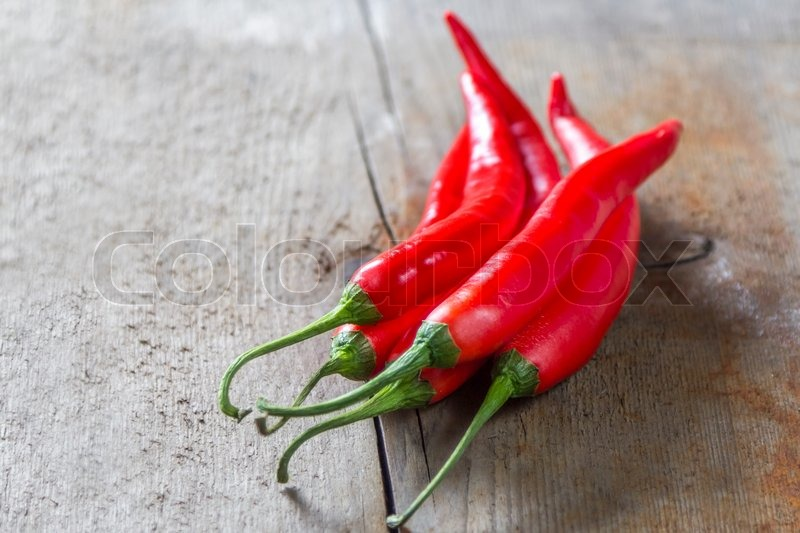 Stock image of 'bunch of red chillies on rustic wooden background'