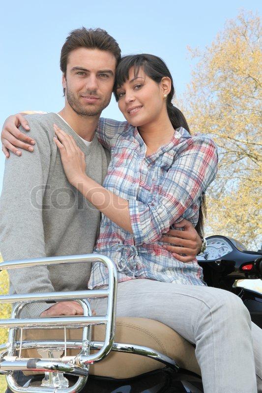 Stock image of 'Couple on a walk with a motorcycle'