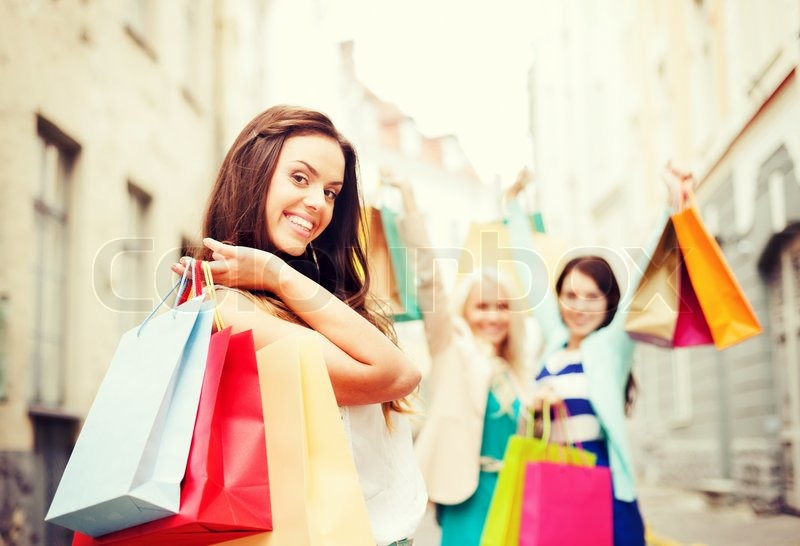 Stock image of 'shopping and tourism concept - beautiful girls with shopping bags in city'