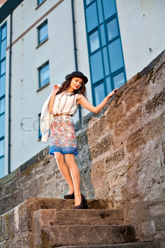 Stock image of 'Young pretty girl elegantly dressed posing on old stone stairs. Cute Caucasian model.'