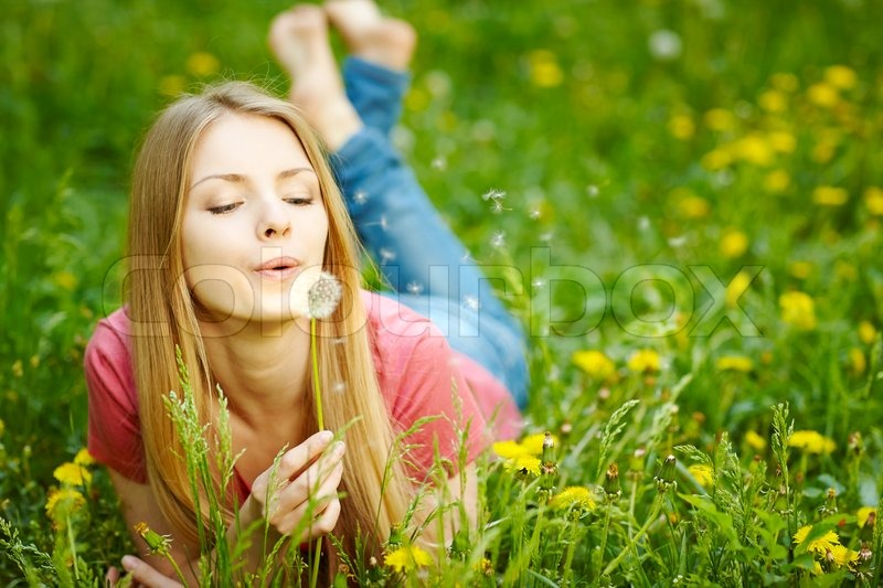 Stock image of 'Womangirl lying on the field of dandelions blowing dandelion, wish concept'