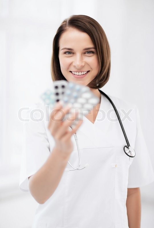 Stock image of 'healthcare and medical concept - doctor with blister packs of pills'
