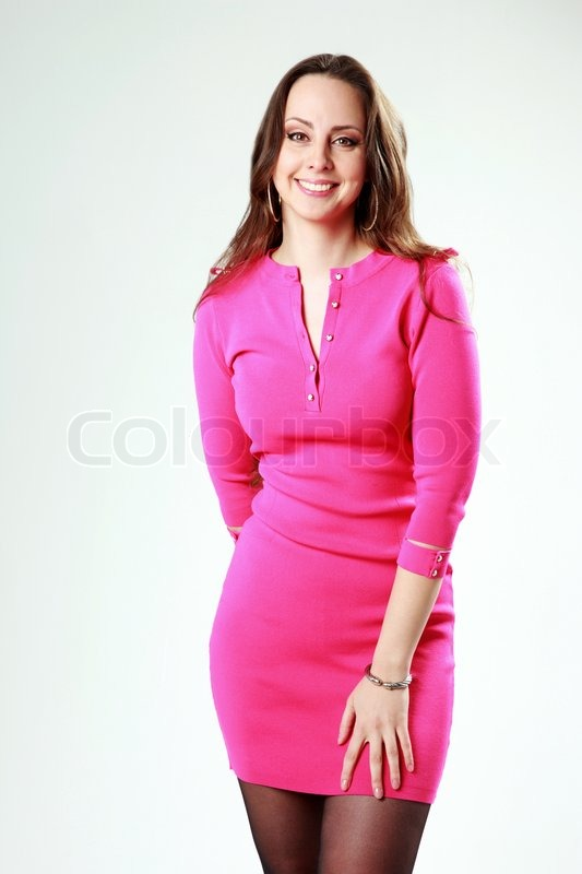 Stock image of 'Portrait of a cheerful woman in pink dress over gray background'
