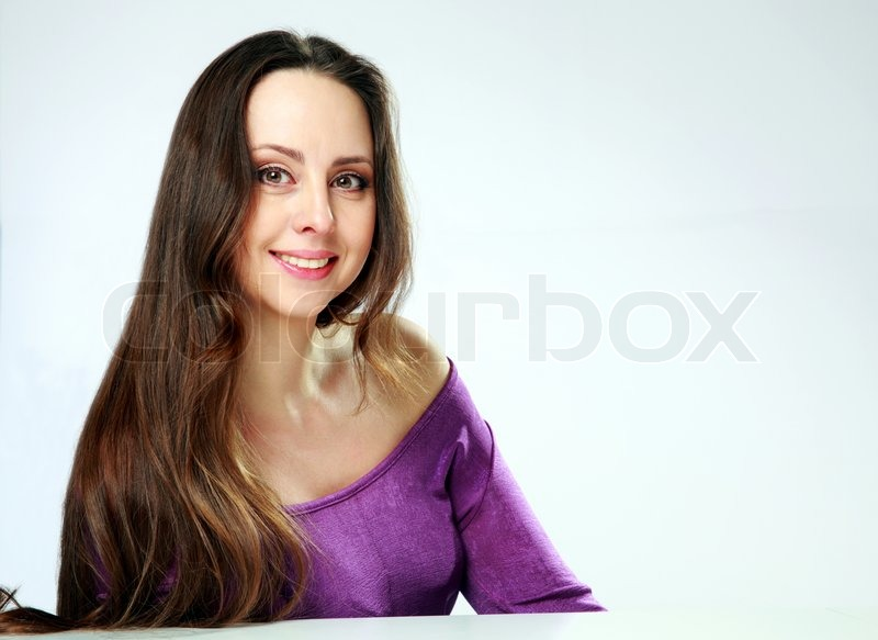 Stock image of 'Portrait of a cheerful woman sitting at the table on gray background'