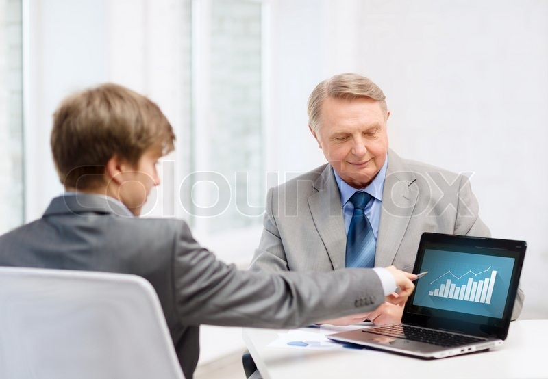 Stock image of 'business, advertisement, technology and office concept - older man and young man with laptop computer in office'