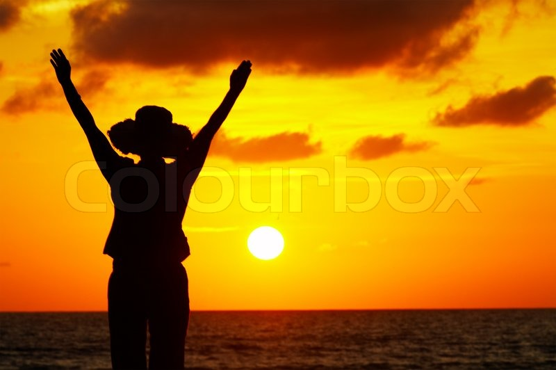 Stock image of 'silhouette of a woman on the beach during sunset'
