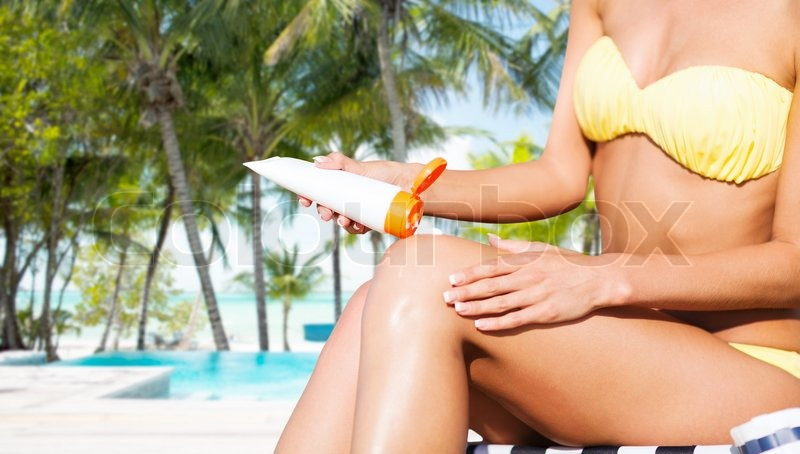 Stock image of 'summer holidays and vacation - girl putting sun protection cream on the beach chair'