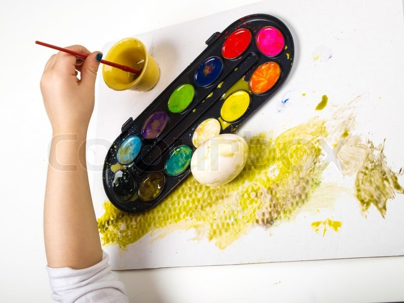 Stock image of 'Little girls hands playing with colorful paint, creating Easter decoration'