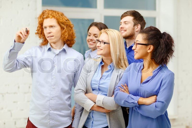Stock image of 'business, office, future technology and startup concept - smiling creative team writing something on virtual screen'