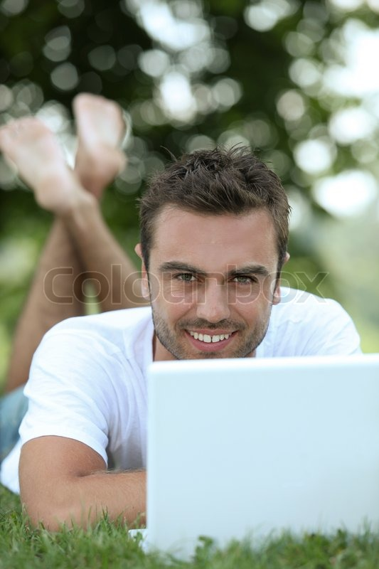 Stock image of 'Young man on laptop'
