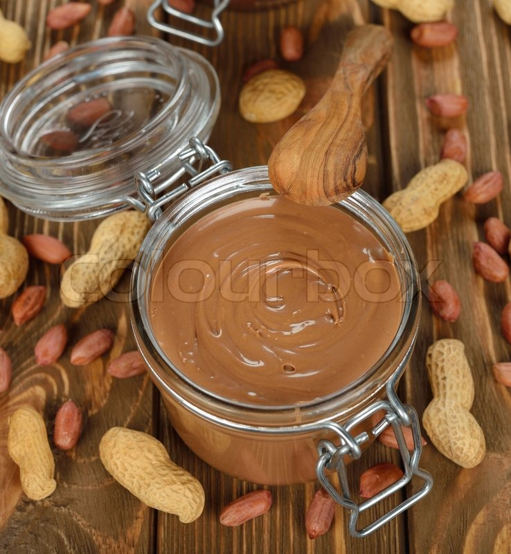 Stock image of 'peanut butter in a glass jar on a brown background'