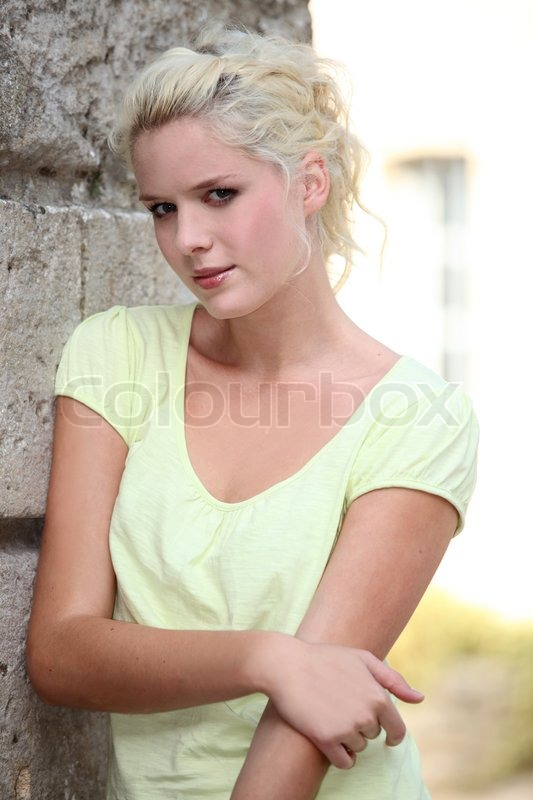 Stock image of 'Pretty young woman standing next to a stone wall'