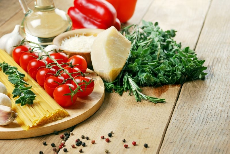 Stock image of 'Pasta ingredients on the wooden table with vegetables and olive oil'