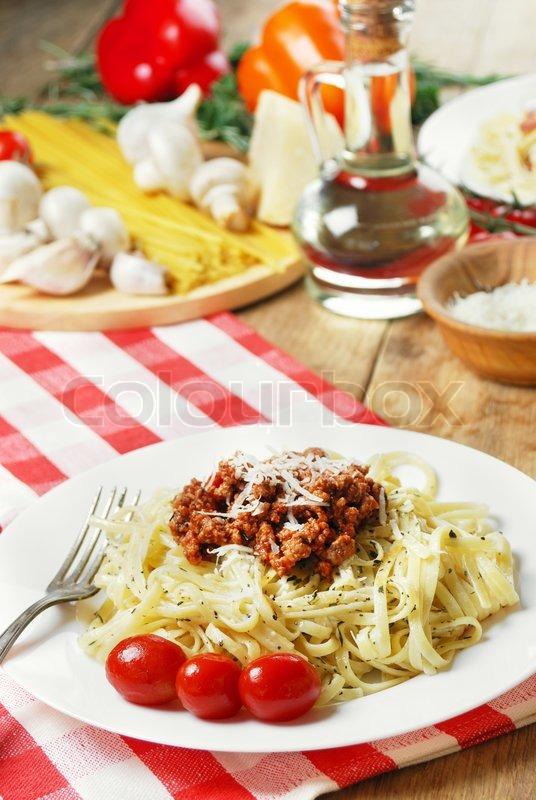 Stock image of 'Pasta bolognese in the white plate on the wooden table with vegetables'