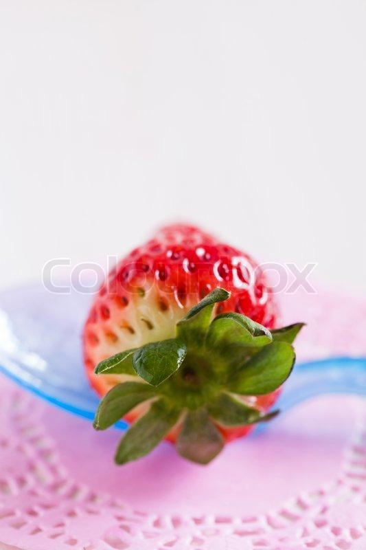 Stock image of 'Closeup of fresh whole strawberry on blue plastic spoon resting on decorative pink mat'