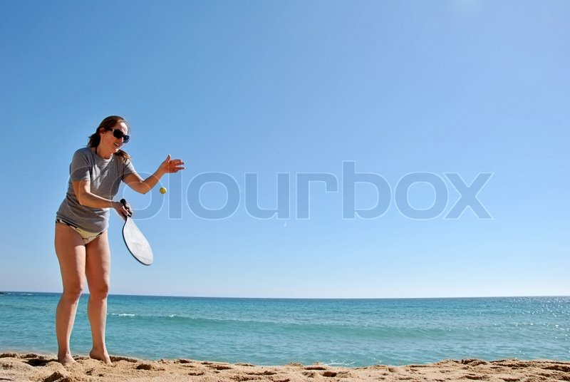 Stock image of 'Cheerful woman playing tennis on the beach'