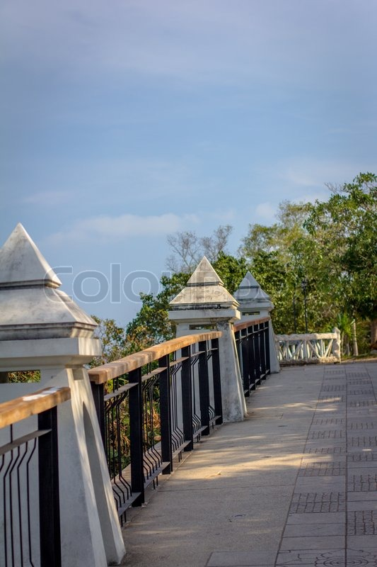 Stock image of 'walkway with columns and trees on the background of sky'