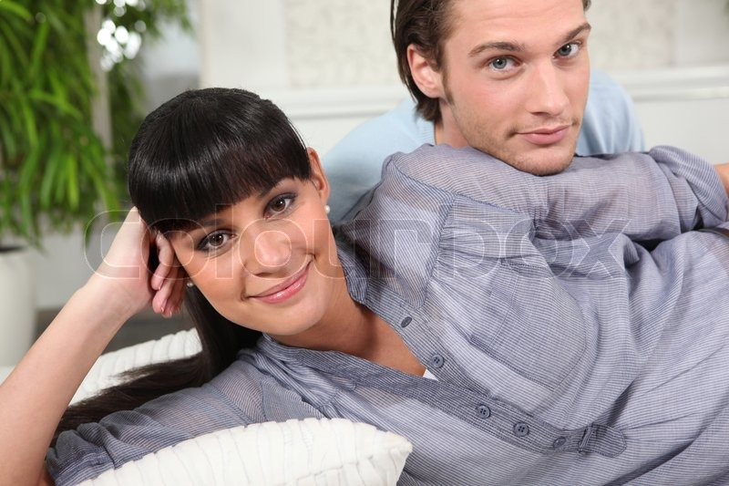 Stock image of 'Smiling woman and young man on sofa'