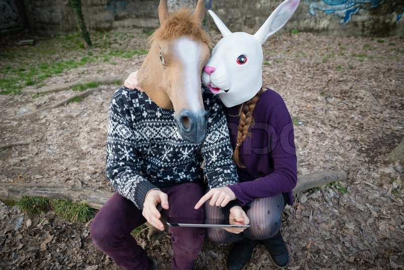 Stock image of 'young hipster cuople horse and rabbit mask using tablet at the park'