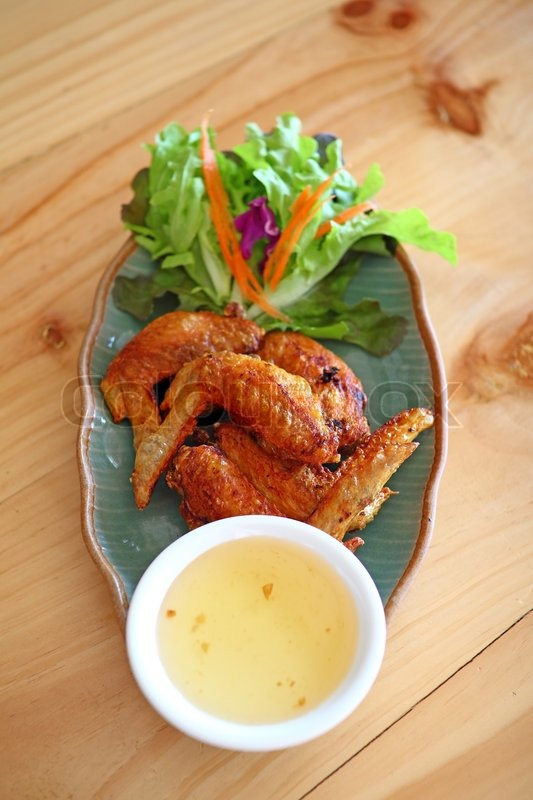 Stock image of 'Wings fied chicken on dish in thai menu on wood table'