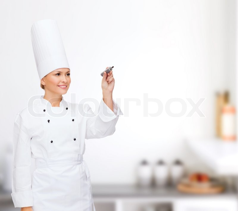 Stock image of 'cooking, new techology , advertisement and food concept - smiling female chef with marker writing something on virtual screen'