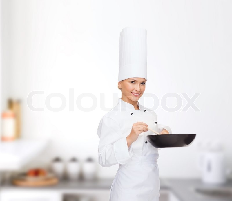 Stock image of 'cooking and food concept - smiling female chef with pan and spoon'