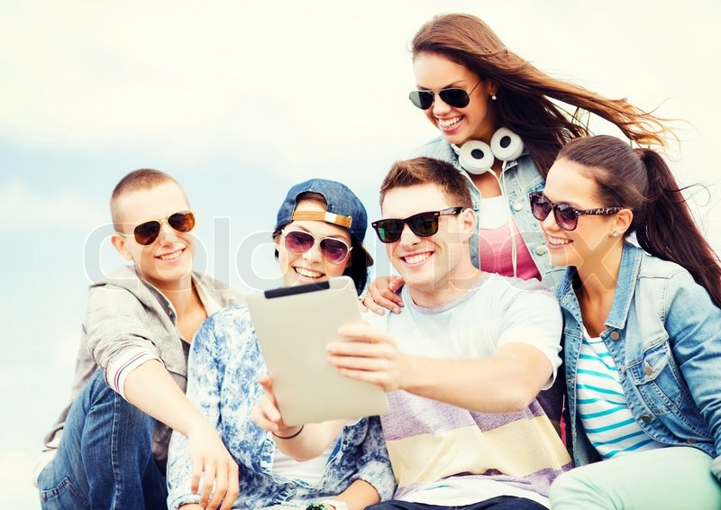 Stock image of 'summer holidays, teenage and technology concept - group of teenagers taking picture with tablet pc'