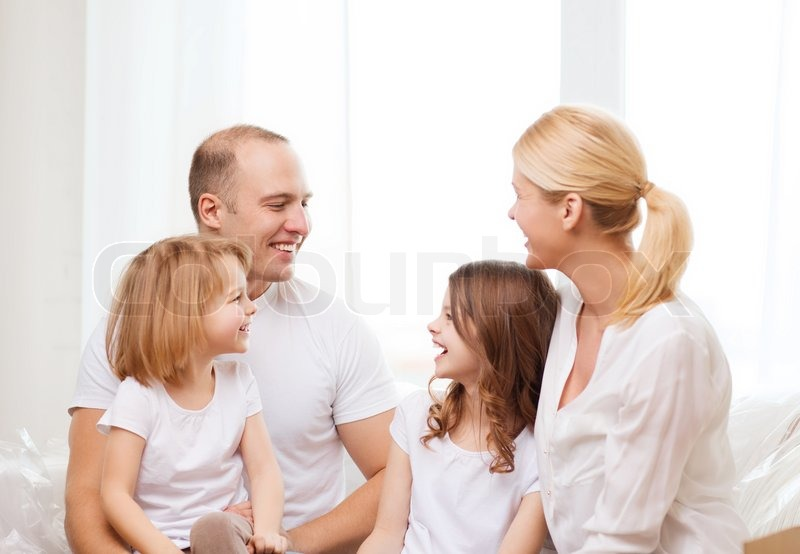 Stock image of 'family, children and home concept - smiling family with two little girls at home'