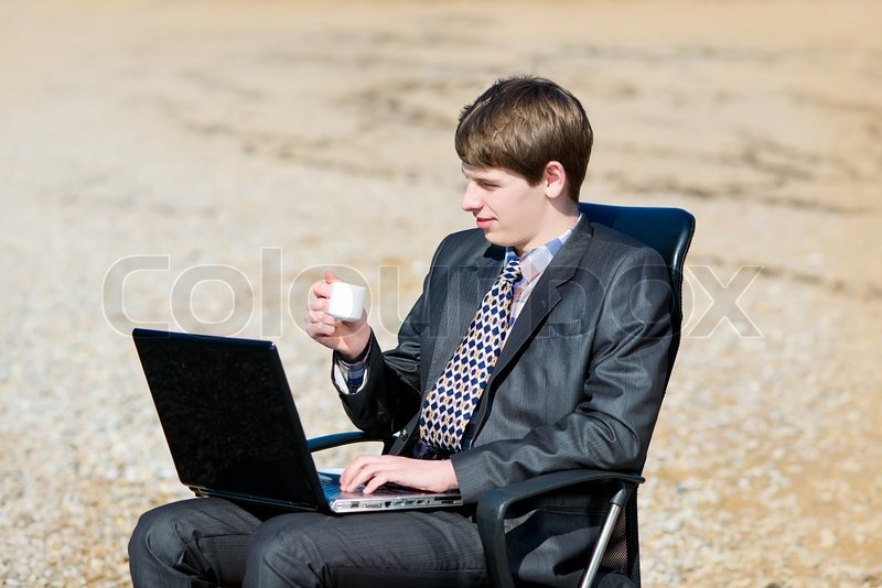 Stock image of 'A man working on a computer outdoors. Freelancer working at a laptop'