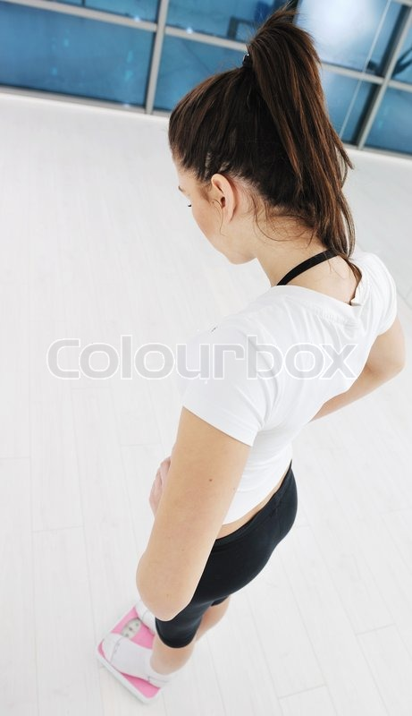 Stock image of 'happy diet concept with young woman on pink scale at sport fitnes gym club'