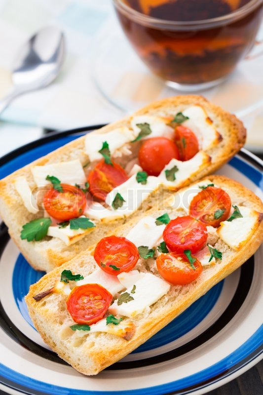 Stock image of 'Vegetarian baguette sandwich with tomato  cheese and herbs'