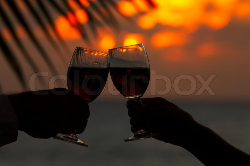 Stock image of 'view of two human's hand with wineglasses during sunset'