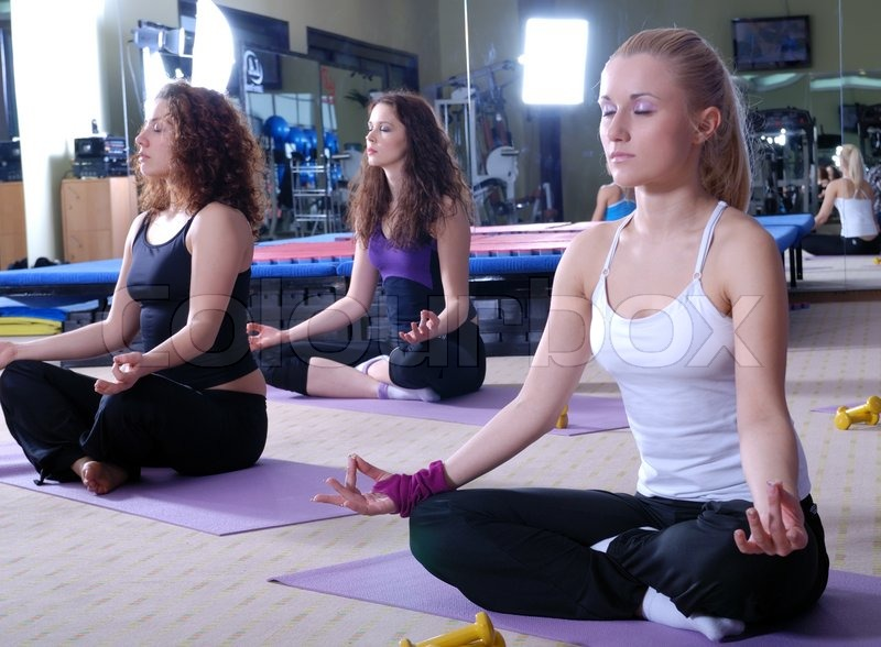 Stock image of 'Beautiful girls meditating in fitness club'