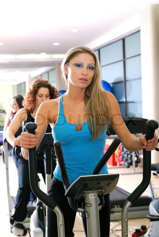 Stock image of 'pretty woman working out at spinning byke at fitness gym'