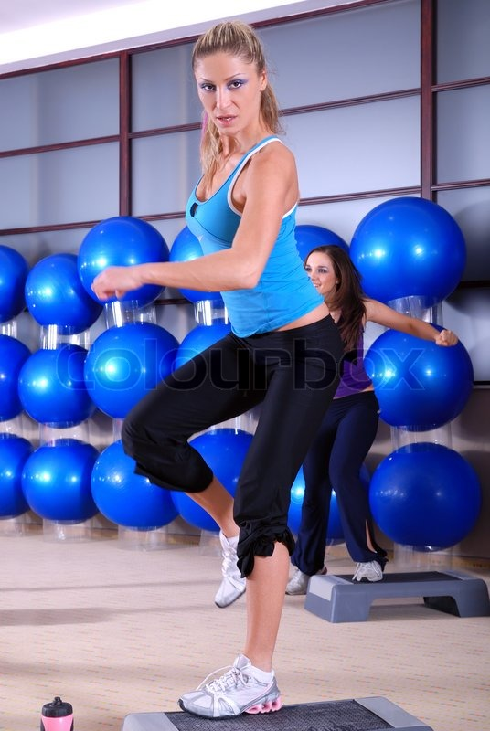 Stock image of 'Woman stepping in a fitness center'