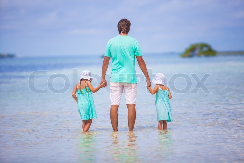 Stock image of 'Rear view of young father and his two adorable daughters on an exotic vacation'