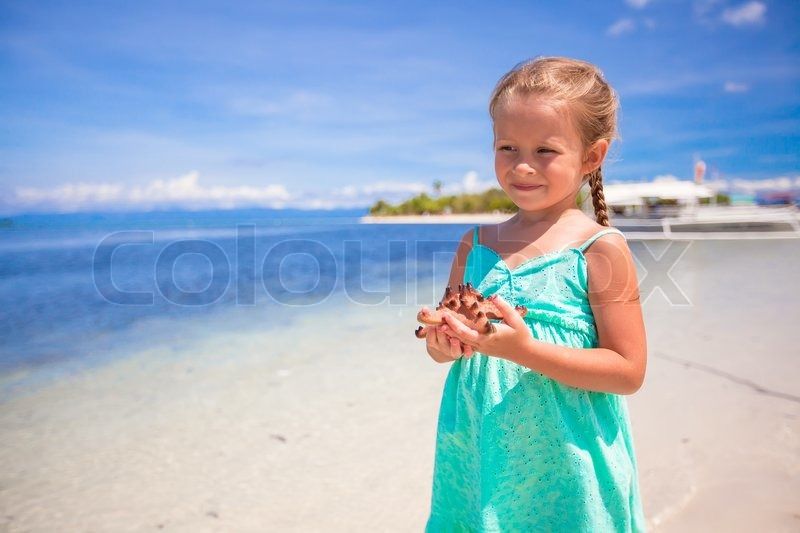 Stock image of 'Little adorable girl with starfish in her hands at the tropical beach'