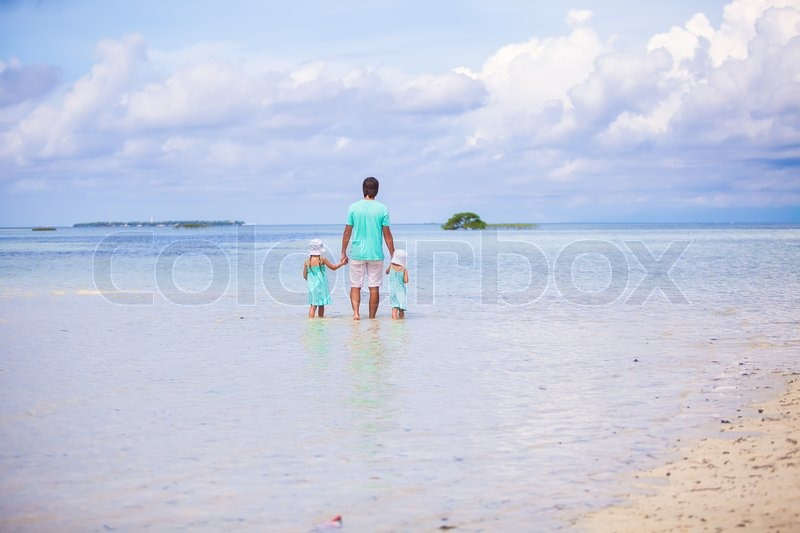 Stock image of 'Back view of adorable little girls and young father walking at exotic island'
