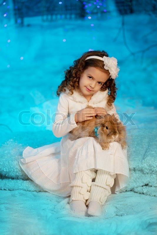 Stock image of 'Little cute winter girl with rabbit'